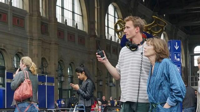 Ein junger Mann steht mit einer älteren Frau in der Zürcher Bahnhofshalle.