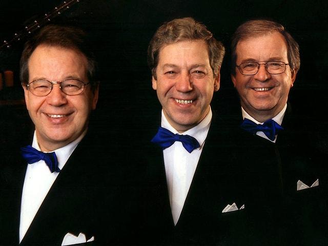 Drei Männer in dunklen Anzügen, weissen Hemden und blauer Fliege.