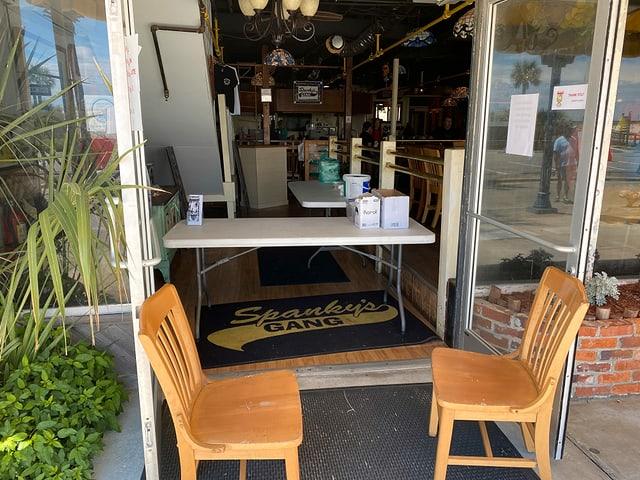 Ein Tisch steht vor einem Restaurant-Eingang.