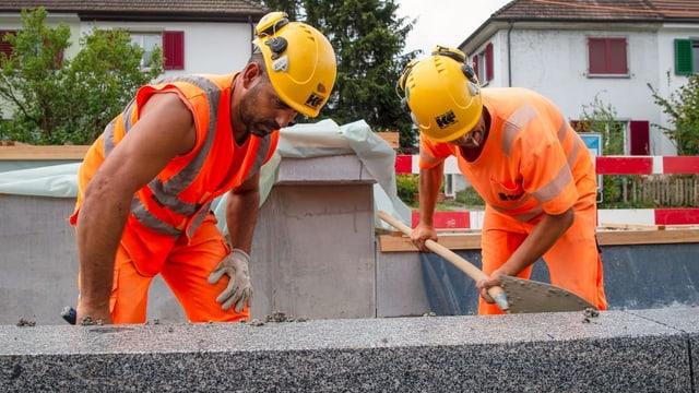 Zwei Bauarbeiter bei der Arbeit an der Limmattalbahnstrecke.
