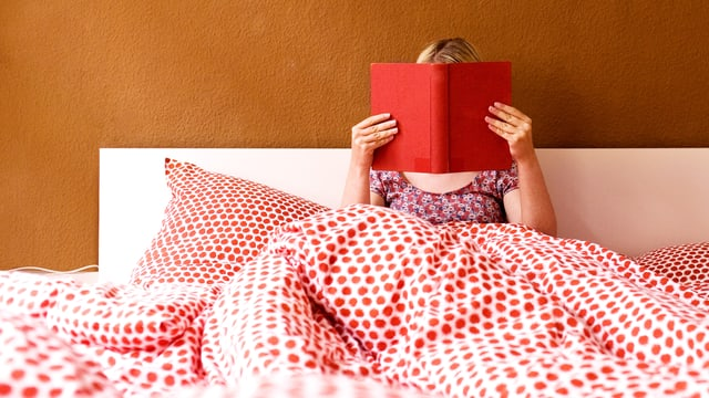 Eine Frau liest im Bett.