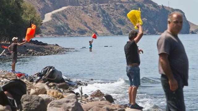 Menschen stehen am Strand und winken mit farbigem Plastik in den Händen aufs Meer hinaus.