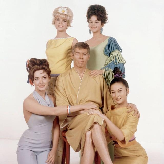 Ein Mann sitzt auf einem Stuhl umrundet von vier schönen Frauen.