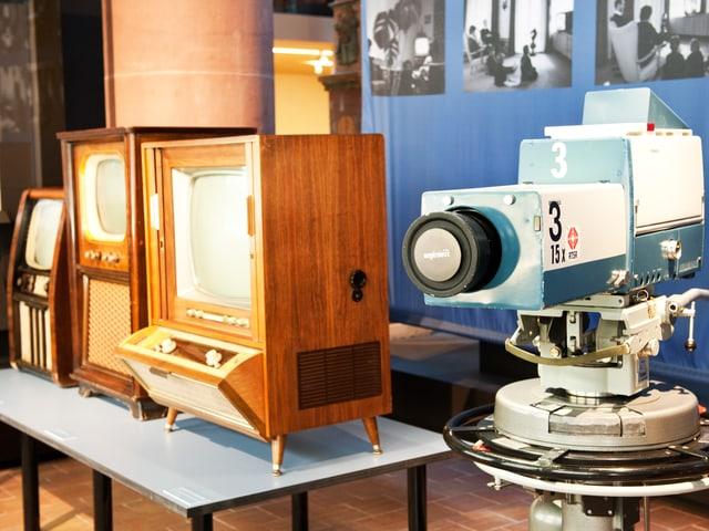 Drei alte Fernsehapparate, die in Holz gekleidet sind, und eine Kamera.