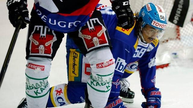 Zwei Eishockeyspieler kämpfen um den Puck. Bierwerbung ziert die Hose des einen und die Schienbeine des anderen.