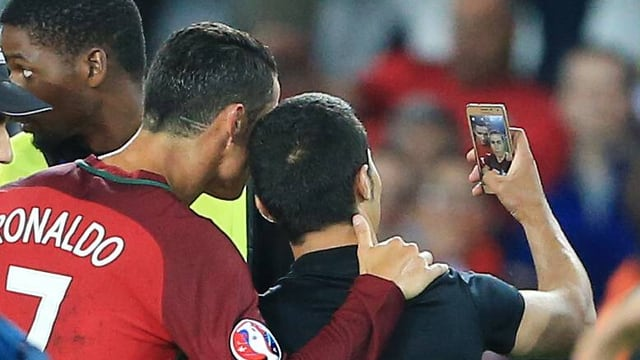 Ronaldo schiesst ein Selfie mit einem Platzstürmer.