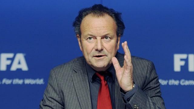 Mark Pieth gestikulierend vor einem Fifa-Logo
