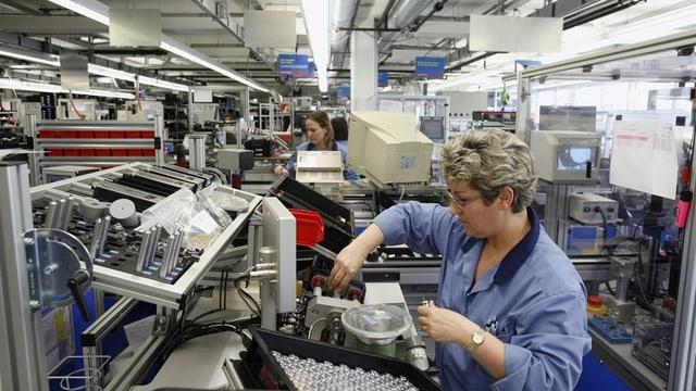 Ein Frau arbeitet in einer Fabrikhalle.