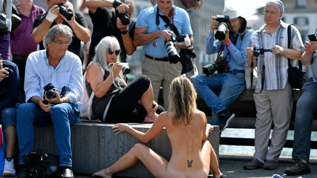 Eine Nacktkünstlerin performt in der Zürcher Innenstadt beobachtet von fotografierenden Männern