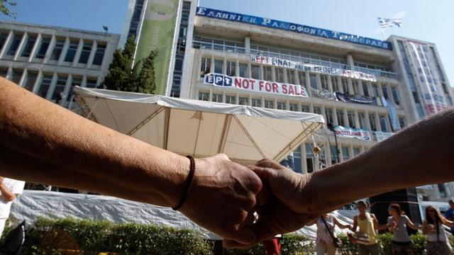 Hände vor dem Gebäude des Staatsfernsehens.