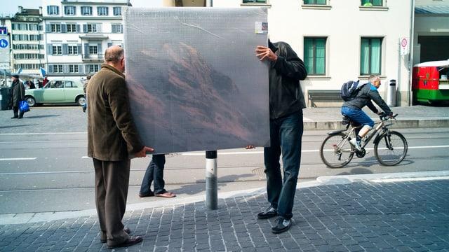 Zwei Männer tragen ein Bild durch die Zürcher Altstadt.