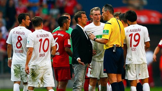 Augsburg-Spieler und ihr Trainer Markus Weinzierl diskutieren mit Schiedsrichter Knut Kircher.