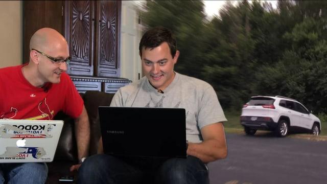 Zwei Männer sitzen auf einem Sofa vor ihren Laptops, rechts im Bild rutscht ein Jeep in einen Graben.