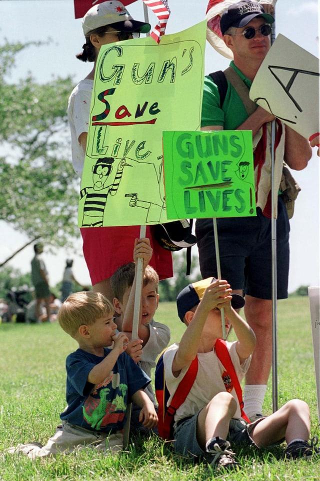 Kinder halten Schilder hoch.