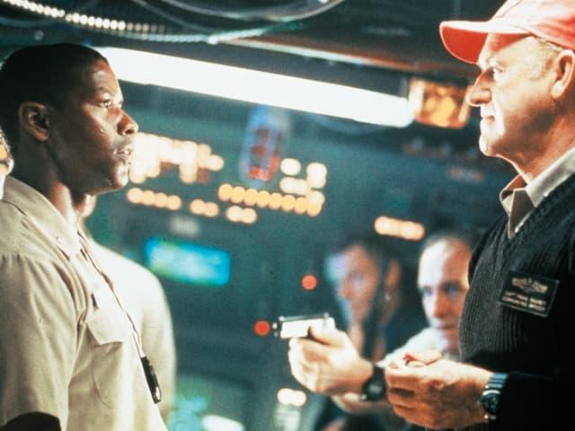 Ron und Frank stehen einander gegenüber, ein Besatzungsmitglied bedroht Ron mit einer Waffe.