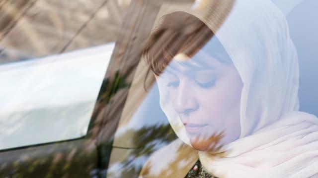 Frau mit Kopftuch sitzt in Auto.