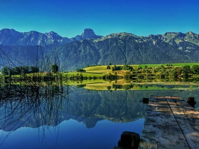 Im spiegelglatten Übeschisee reflektiert das herrliche Bergpanorama.