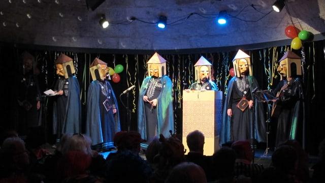 Männer in blauen Gewändern und mit Turm-Masken.