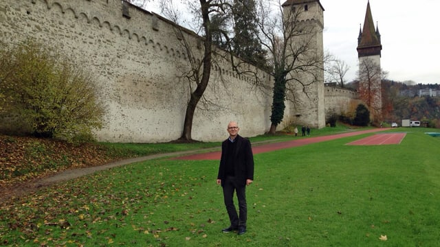 Mann vor Stadtmauer mit Türmen.