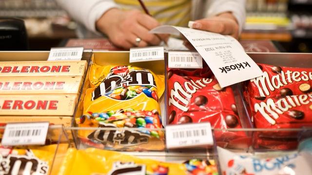 Auslage eines Kiosks mit Toblerone, M&Ms und Maltesers. Eine Frau prüft einen Kassenbon.