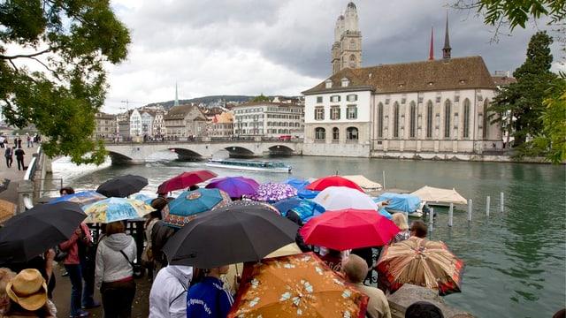 Gruppe von Touristen mit Regenschirmen am Limmatufer, im Hintergrund das Grossmünster