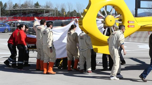 McLaren-Mitarbeiter schirmen mit Tüchern Fernando Alonso ab.