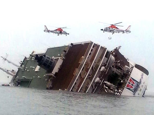 Die «Sewol» liegt mit Schlagseite halb unter Wasser, zwei Rettungshelikopter schweben über dem Schiff