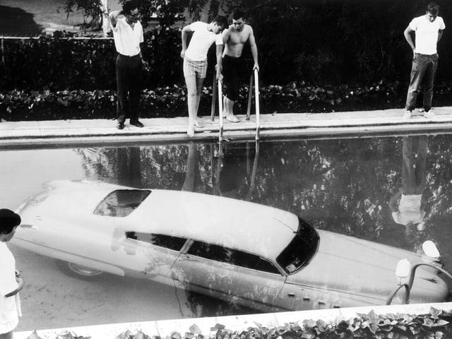 Auto am Boden eines Pools, darum stehen Menschen