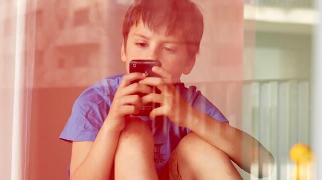 Ein Kinde liest eine Nachricht auf seinem Handy.