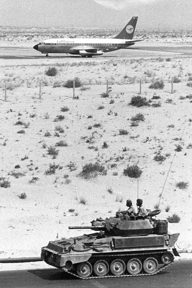 Flugzeug von Panzer bewacht.
