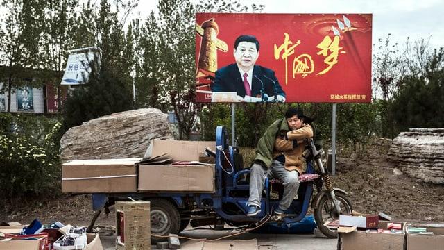 Ein Händler präsentiert seine Waren, im Hintergrund ein Plakat, auf dem Ministerpräsident Xi Jinping zu sehen ist.