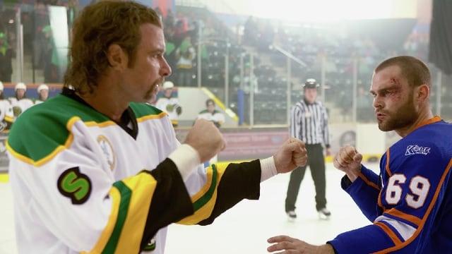 Zwei Männer im Eishockey-Dress stehen sich mit erhobenen Fäusten gegenüber.
