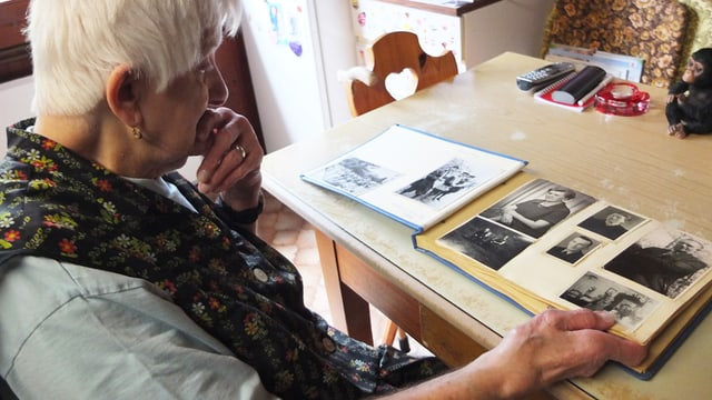 Frau blättert in einem Album mit alten Fotos.