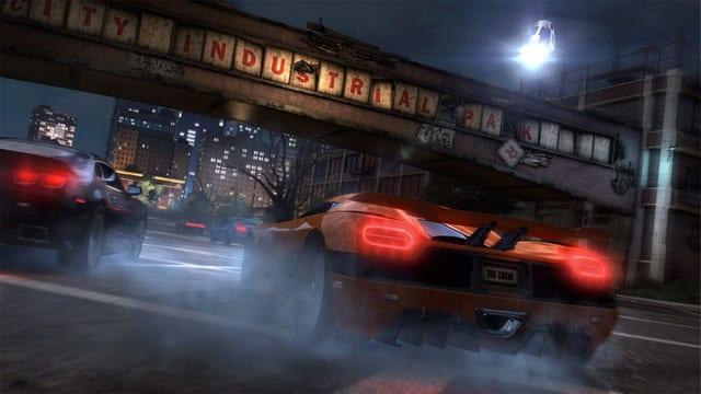 Autos liefern sich bei Nacht in einer Stadt ein Rennen.