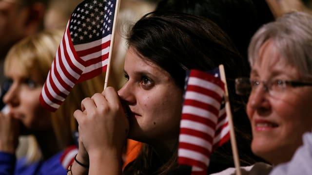 Gerührte Zuschauer mit kleinen USA-Flaggen in der Hand