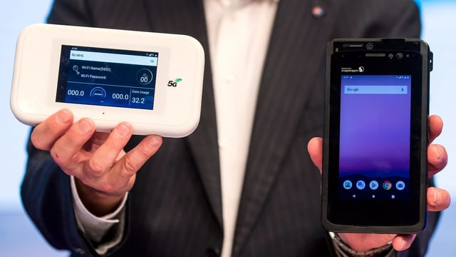Ein Vertreter der Swisscom zeigt den Prototypen eines 5G-fähigen Smartphones von Qualcomm (rechts).