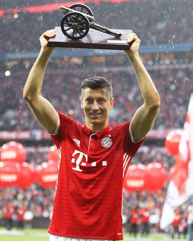 Fussballer mit Pokal in der Hand.