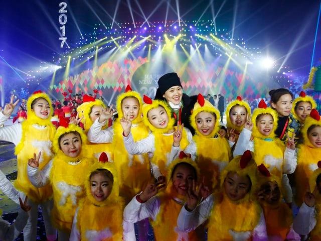 Chinesische Mädchen in Hahn-Kostümen.