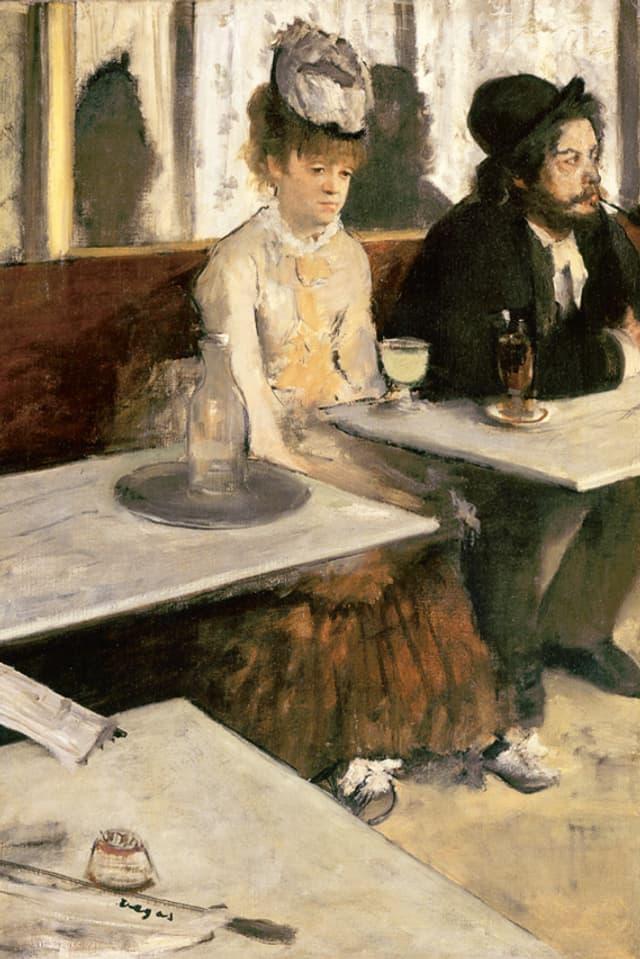 Eine Frau sitzt im Cafe vor einem Glas und starrt ins Leere.