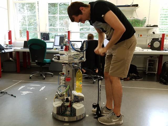 Ein junger Mann pumpt mit einer Velopumpe eine Petflasche auf, die am Roboter montiert ist.