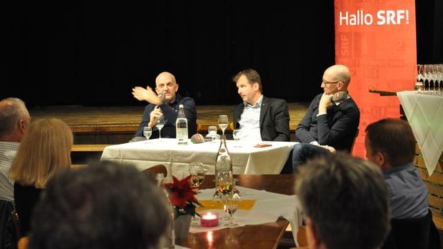 Drei Männer sitzen an einem Tisch. Im Hintergrund das Hallo SRF Logo