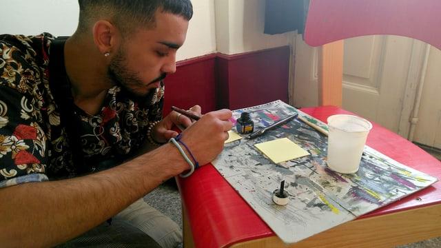 Ein junger Mann zeichnet ein Bild.
