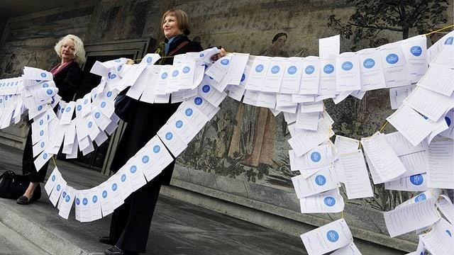Zwei Frauen und ein Mann stehen auf einer steinigen Treppe, zwischen sich eine Girlande aus weissen Papierblättern.