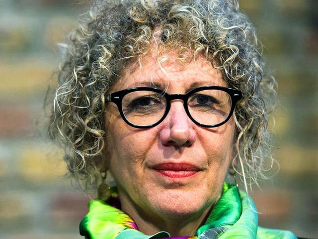 Eine Frau mit einem blonden Lockenkopf und schwarzer Brille.