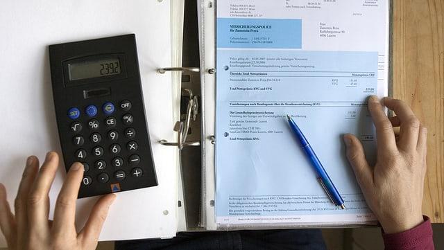 Krankenkassenrechnung, Taschenrechner, Bleistift, Hände tippen auf Rechner.