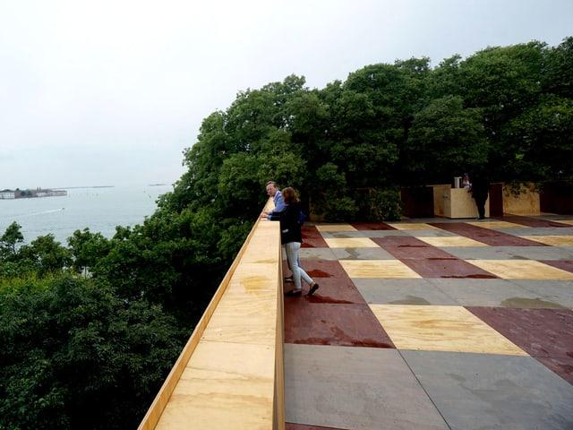 Zwei Menschen stehen auf einer Terrasse.