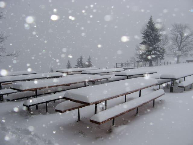 Bänke und Stühle sind von 30 Zentimeter Neuschnee bedeckt, es schneit stark.
