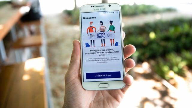 Hand mit Handy, auf dem die Tracing-App sichtbar ist