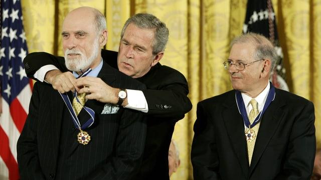 George W. Bush legt Vint Cerf von hinten eine Medaille um den Hals, Bob Kahn schaut rechts davon stehend skeptisch zu.