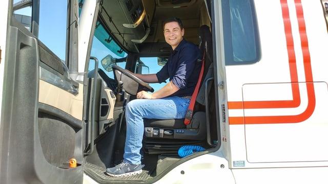 Ein Mann sitzt am Steuer eines Lastwagens.